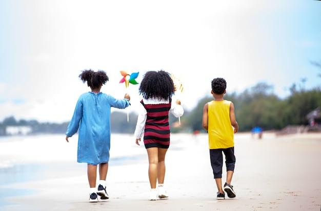 Bambini che giocano a correre sulla sabbia in spiaggia, un gruppo di bambini che si tengono per mano in fila sulla spiaggia in estate, vista posteriore contro il mare e il cielo blu