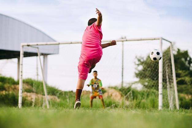 Bambini che giocano a calcio per fare esercizio sul campo in erba verde