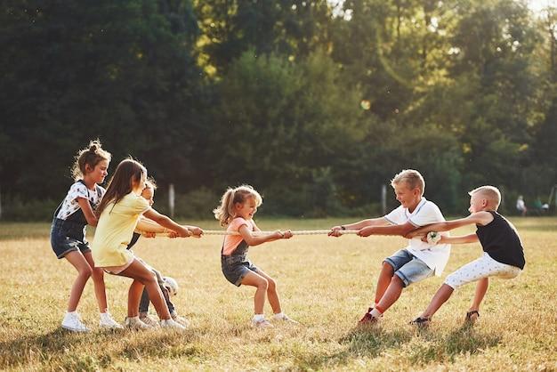 Bambini che giocano al tiro alla fune nel bellissimo prato al giorno di sole.