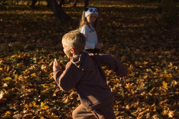 Bambini che corrono nel parco d'autunno