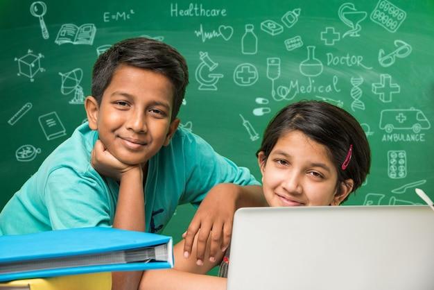 Bambini e concetto di scienza - carino studente indiano o scienziato che studia scienza o sperimenta con microscopio e prodotti chimici con diagrammi scarabocchi disegnati su lavagna verde