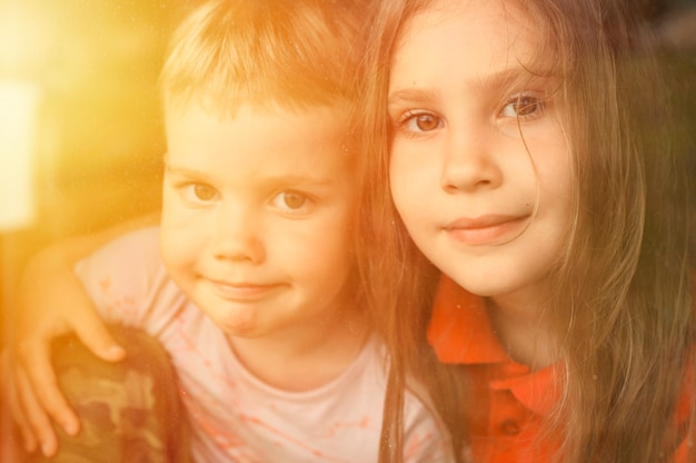 Fratelli e sorelle bambini ragazzo e ragazza guarda attraverso la finestra durante la quarantena covid-19. resta a casa, stiamo tutti bene. bagliore