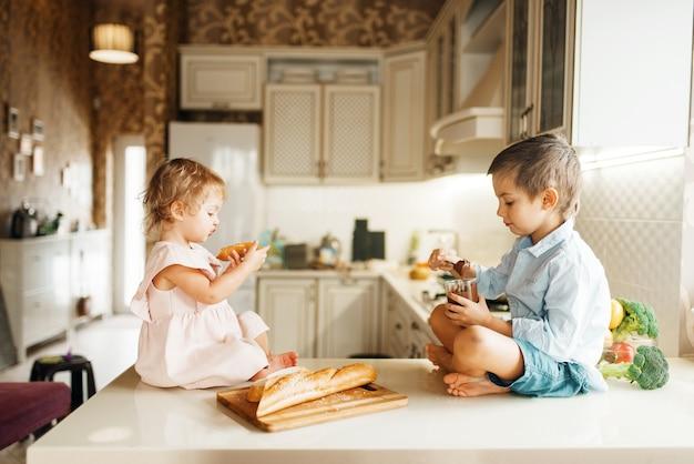 I bambini spalmano il cioccolato fuso sul pane