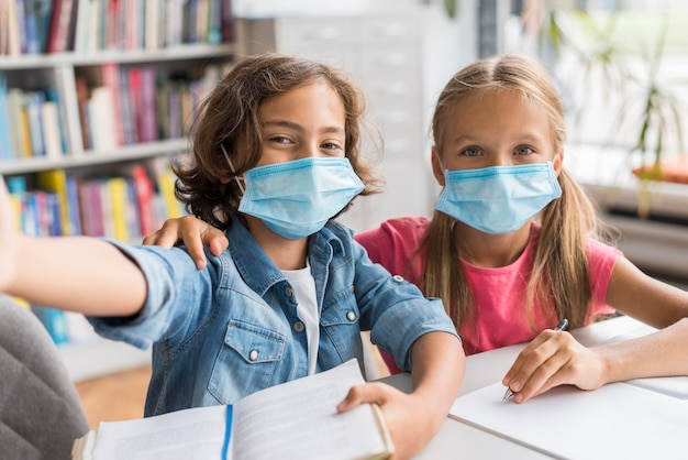 Bambini che si fanno un selfie in biblioteca mentre indossano maschere mediche