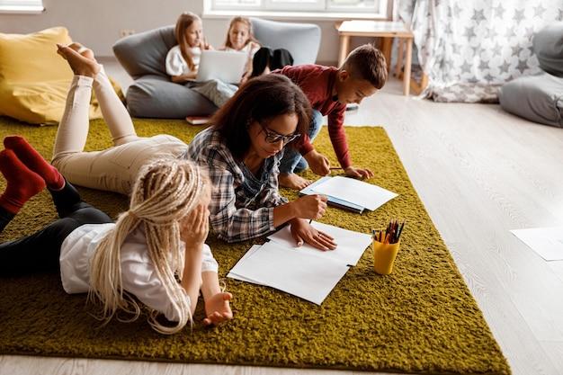 Bambini e insegnante che disegnano insieme a scuola
