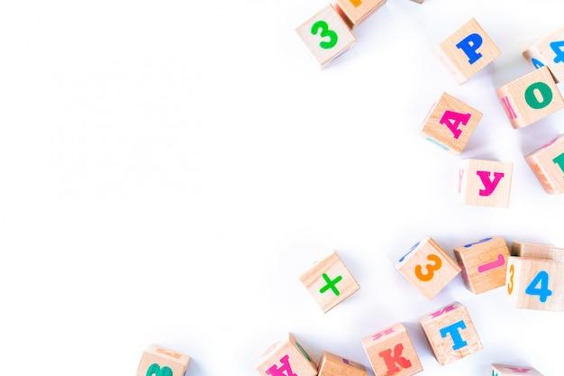 I bambini gioca i cuccioli di legno con le lettere e numeri su fondo bianco. lo sviluppo di blocchi di legno. giocattoli naturali ed ecologici per bambini. vista dall'alto. disteso. copia spazio.