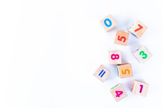 I bambini gioca i cuccioli di legno con le lettere e numeri su bianco