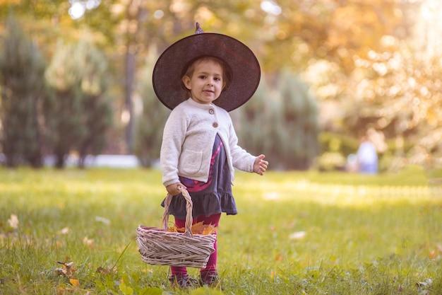 Bambini dolcetto o scherzetto nella notte di halloween bambina con zucca faccia caramella secchio bambino trucco o