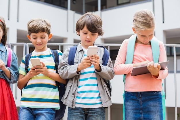 Bambini che utilizzano il telefono cellulare e la tavoletta digitale sul terrazzo della scuola