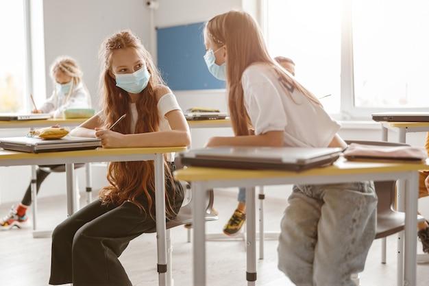 Bambini che usano matite e quaderni mentre scrivono test insieme a scuola