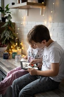 I bambini si videochiamano a vicenda per rimanere in contatto durante la pausa invernale. ragazzino con cappello da babbo natale seduto davanti allo schermo del computer, chattando online con un gruppo di suoi diversi amici alla vigilia di natale a casa