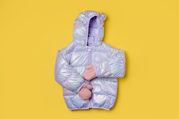 Piumino da bambino caldo con cappuccio su sfondo rosa. capispalla per bambini alla moda. vestito alla moda invernale