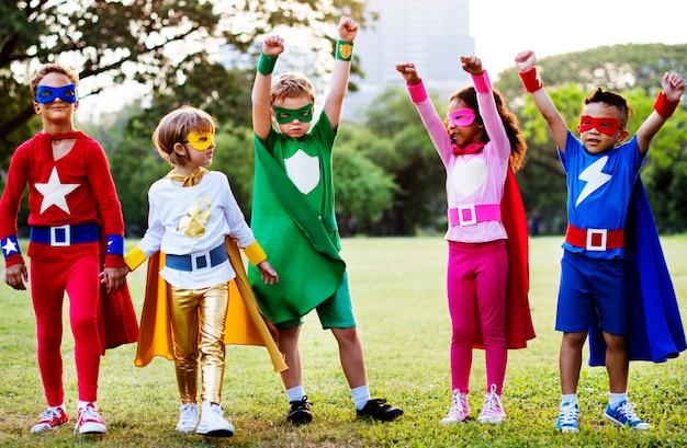 I bambini indossano il costume da supereroe all'aperto