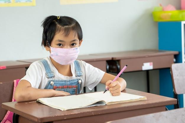 Bambini che indossano una maschera per la sicurezza contro il coronavirus in classe