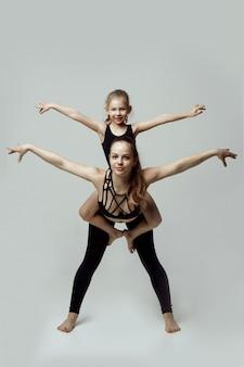 Bambini con insegnante femminile che addestra una bambina, praticando ginnastica, in piedi in esercizio. acrobatico in sfondo bianco loft studio