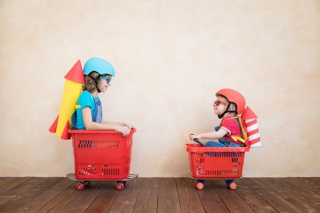 Bambini con razzo di carta che corre sul carrello della spesa al coperto
