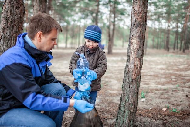 Bambini con la loro area di pulizia del padre nella foresta vicino alla spiaggia