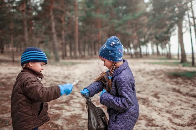 Bambini con la loro area di pulizia del padre nella foresta