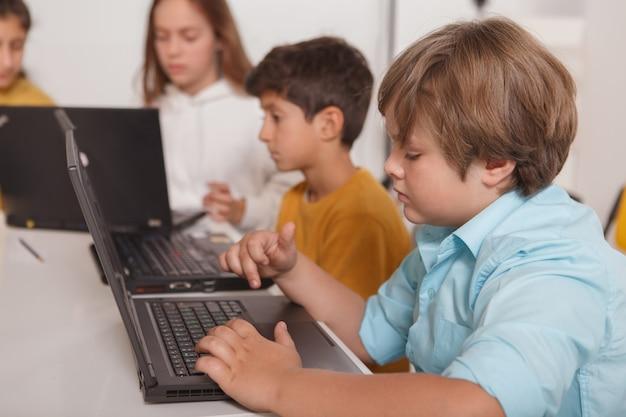 Bambini che lavorano al computer portatile a scuola di computer