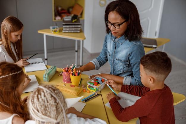 Bambini che scrivono sui quaderni seduti a tavola con l'insegnante