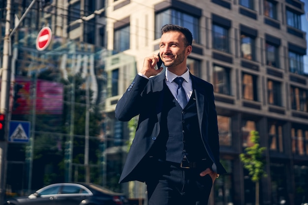 Persona di sesso maschile con la barba gentile che sorride mentre parla al telefono
