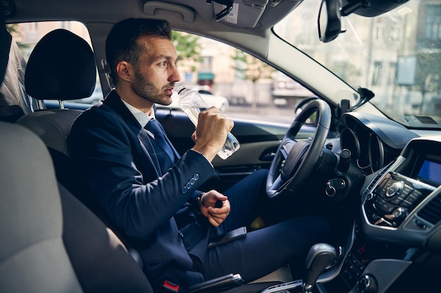 Gentile uomo con la barba che indossa un costume ufficiale e seduto nella sua macchina, bevendo acqua fresca
