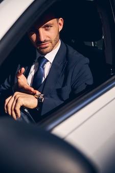 Gentile uomo d'affari che indica i suoi nuovi orologi, essendo nella sua auto mentre guida verso il centro affari Foto Premium