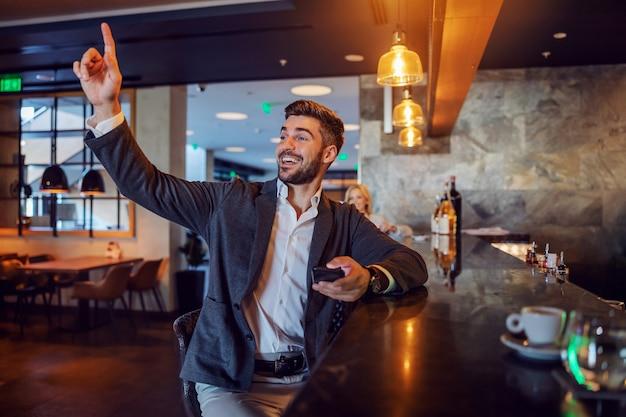 Un uomo d'affari gentile siede in un bar chiedendo un assegno. chiama il cameriere con una mano mentre tiene il telefono nell'altra. atteggiamento positivo, tempo di pausa, pausa, rete di social media