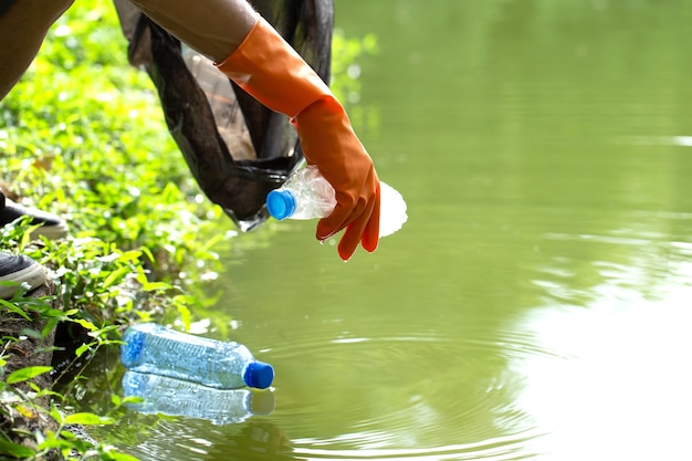 Gentili volontari ecologici che tengono in mano pacchetti e raccolgono rifiuti di bottiglie di plastica dall'acqua