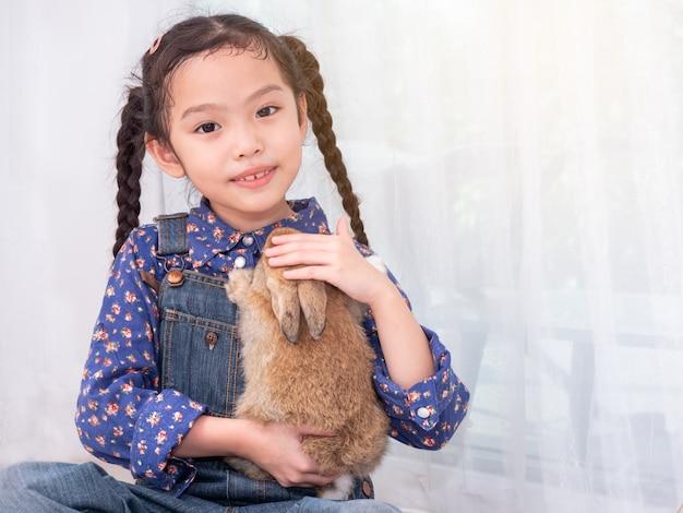 Gentile bambina carina di 6 anni seduta e in possesso di un coniglio marrone.