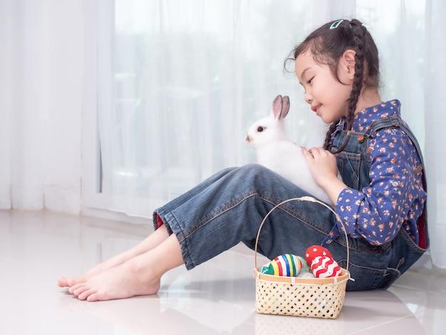 Gentile bambina carina di 6 anni seduta e in possesso di un coniglio bianco con cesto di uova di pasqua.