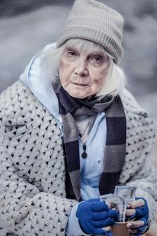 Persone gentili. donna senzatetto triste che è grata mentre riceve aiuti finanziari dalle persone