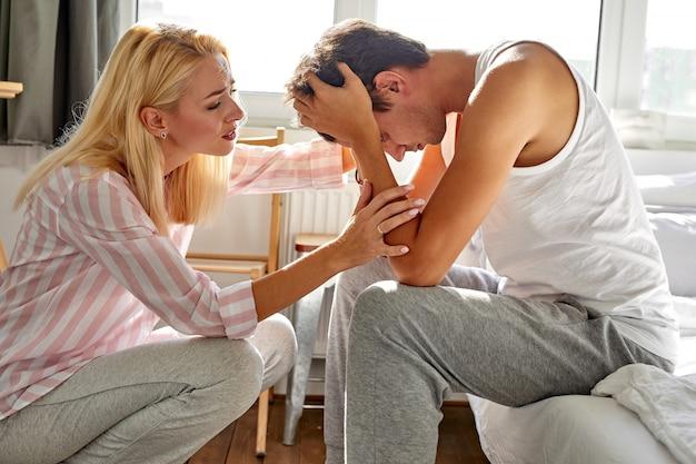 La donna gentile sostiene il marito a casa, la donna parla con l'uomo seduto con la testa china, in camera da letto