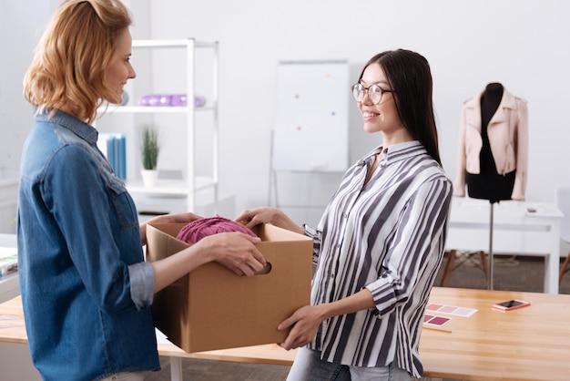 Gentile giovane donna che porta via una scatola dal suo collega, aiutandola a portarla mentre il suo collega la guarda con un sorriso grato