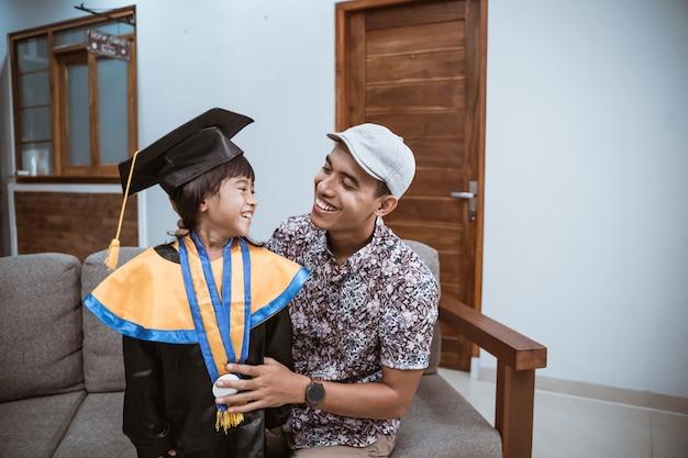 Il padre asiatico di laurea dell'asilo abbraccia sua figlia