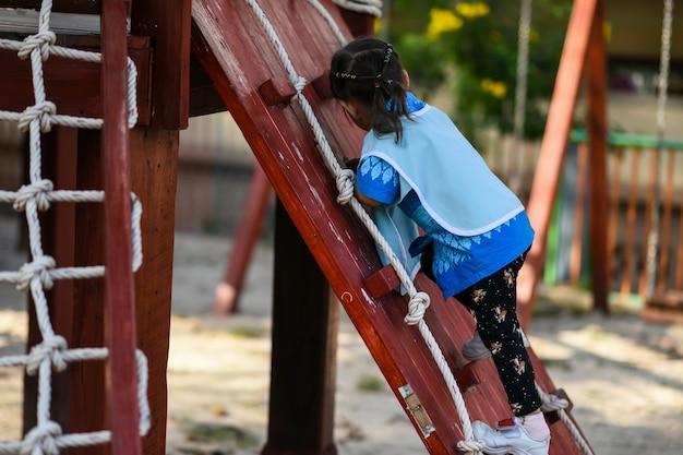 La bambina dell'asilo si arrampica dal pendio di legno del parco giochi per bambini in estate con luce naturale