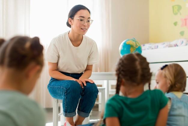 Maestra d'asilo che spiega qualcosa agli studenti