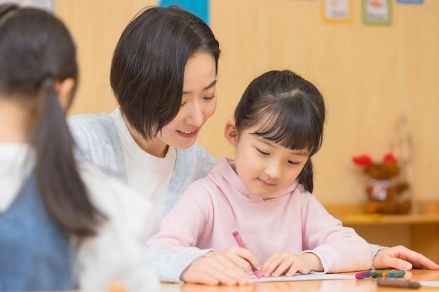 Maestra d'asilo che gioca con i bambini