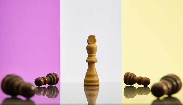 King è l'ultimo pezzo degli scacchi in piedi, circondato da pedine nere cadute. concetto di perseveranza, immunità e resilienza.
