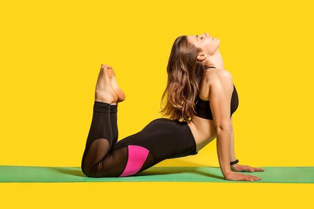 Posa del re cobra. montare la donna in abiti sportivi attillati praticando yoga, facendo esercizio bhujangasana sollevando le gambe per raggiungere la testa, allungando i muscoli per una migliore flessibilità. girato in studio, allenamenti sportivi isolati