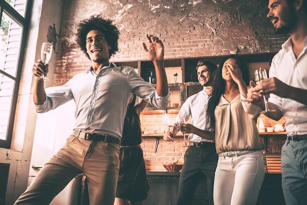 Re della danza. inquadratura dal basso di giovani allegri che ballano e bevono mentre si godono la festa a casa in cucina