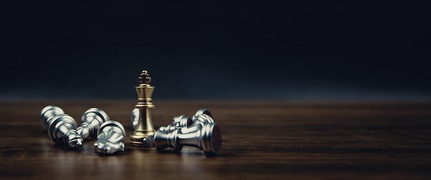 Scacchi re d'oro in piedi nel mezzo degli scacchi d'argento che cadono.