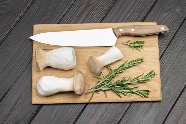 Re funghi ostrica e coltello sul tagliere