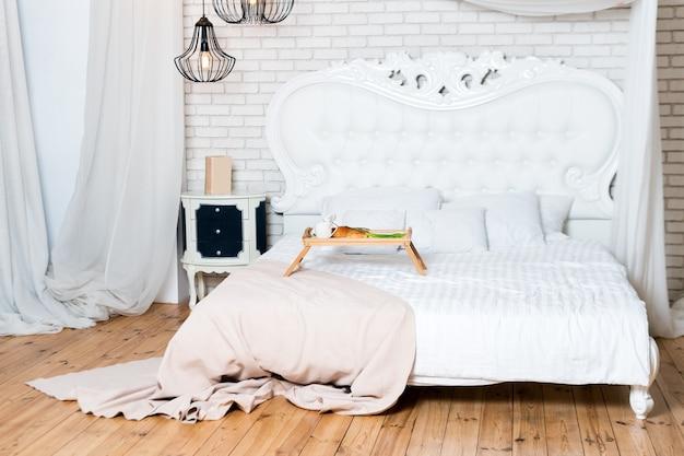 Letto king size in appartamento loft, colazione a letto, vassoio di caffè, croissant e fiori, luna di miele, mattina presto in hotel.