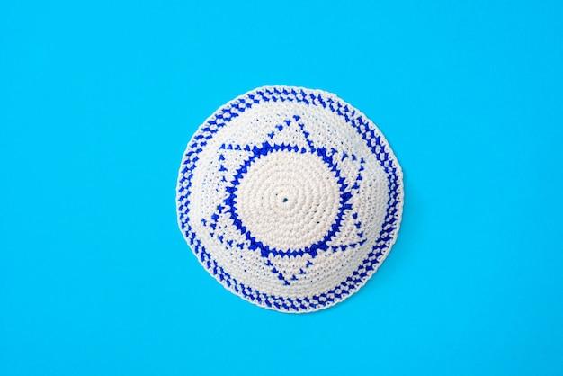Kippah è un cappello circolare, con la bandiera di israele, isolato su sfondo blu.