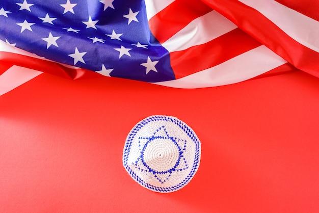 Kippah con la bandiera israeliana, accanto a una bandiera americana, gli stati uniti sono un paese protettivo di israele.