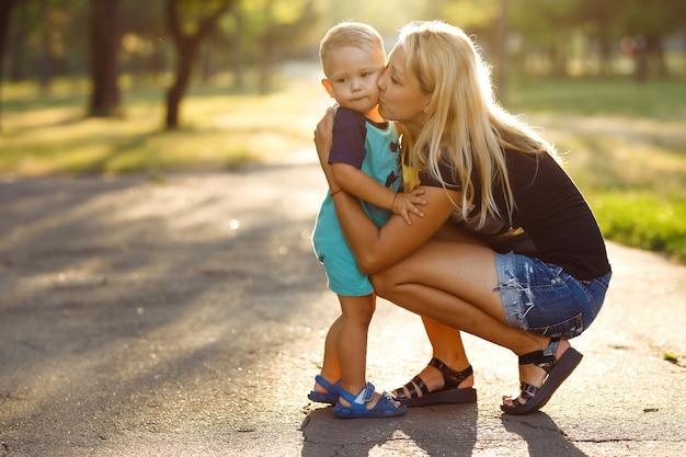 Bacio e abbracci di mamma e figlio. mamma e figlio camminano nel parco estivo.