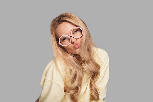 Labbra da baciare. bella giovane donna in occhiali rosa che si increspa mentre sta in piedi su uno sfondo grigio