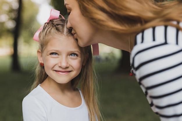 Figlia che bacia. madre amorevole dai capelli biondi che si sente incredibilmente allegra mentre bacia la sua ragazza carina in età prescolare