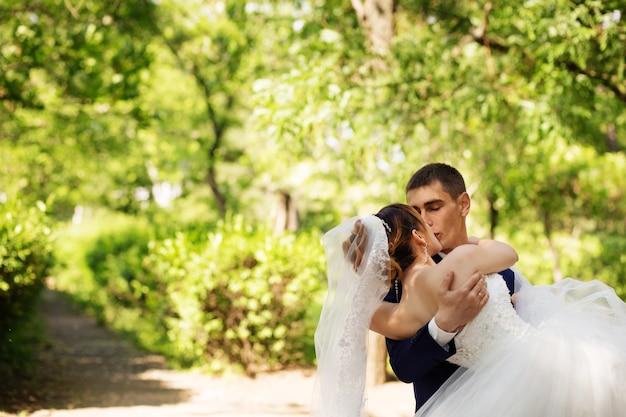 Baciare gli sposi innamorati, la sposa e lo sposo che si baciano nel parco